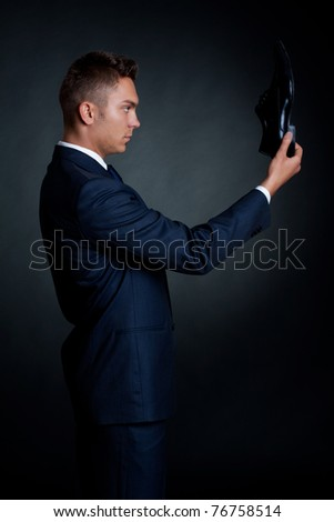 portrait of a stylish man in an elegant suit and shoes in hand - stock photo