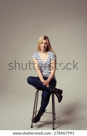 Portrait of a Stylish Pretty Girl in Trendy Attire Sitting on a Bar Stool with Legs Crossed on a Brown Background. - stock photo