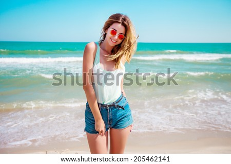 Portrait of a stylish sexy girl in sunglasses and jeans shorts. Resting on a paradise beach, enjoying the sun. - stock photo
