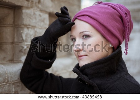 Portrait of a stylish woman near the brick wall