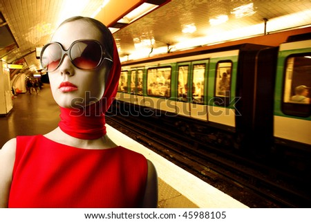 Portrait of a stylish woman standing on the platform of an underground station - stock photo