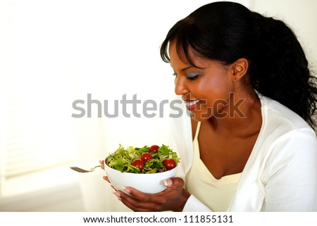 Portrait of a stylish young black woman smiling and looking to a green salad. With copyspace. - stock photo