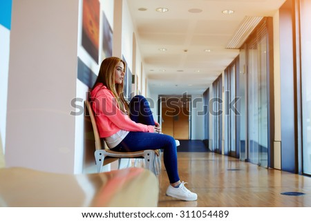 Portrait of a stylish young hipster girl sitting in university corridor waiting the begin of lectures, female college student looking thoughtful and pensive, copy space area for your text message - stock photo