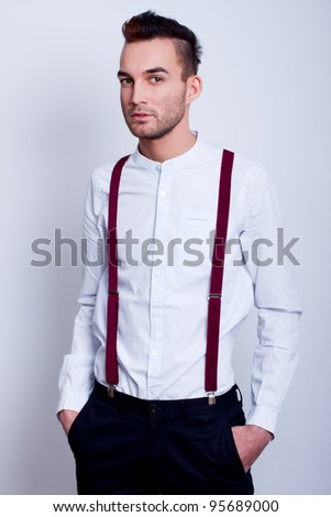 portrait of a stylish young man in white shirt and suspenders against white background - stock photo