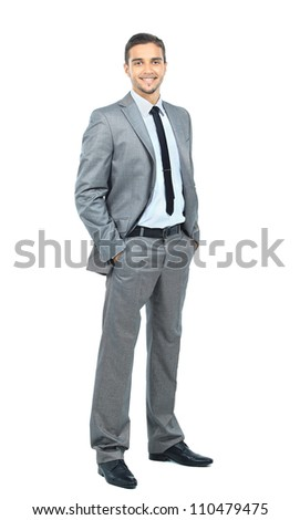 Portrait of a stylish young man standing with hands folded over white background - stock photo