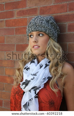 portrait of a stylish young woman against a brick wall. - stock photo