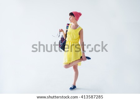 Portrait of a stylish young woman in pink hat and with backpack isolated on a white background - stock photo