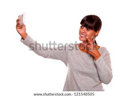 Portrait of a stylish young woman taking a photo with her cellphone against white background - stock photo