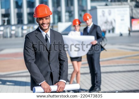Portrait of a successful architect. Confident and smiling African architect holding blueprints in hand while standing on the construction site with his colleagues in the background - stock photo