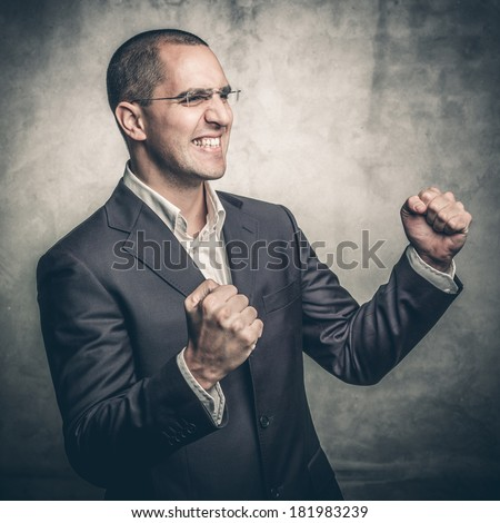 Portrait of a successful business man with hands in the air, celebrating a victory. Lots of energy. - stock photo
