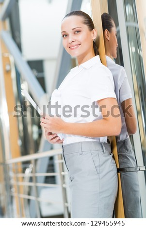 Portrait of a successful business woman in the office, holding papers and looking into the camera - stock photo