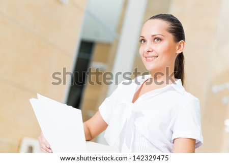 Portrait of a successful business woman in the office, holding papers and smile