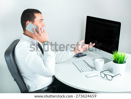 portrait of a successful businessman at office using mobile phone - stock photo