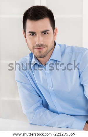 Portrait of a successful businessman in blue shirt sitting in his office.