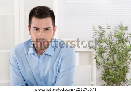 Portrait of a successful businessman in blue shirt sitting in his office. - stock photo