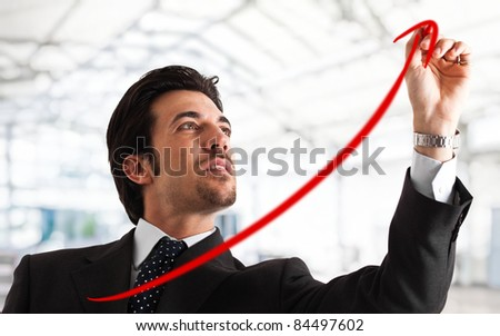 Portrait of a successful handsome businessman drawing a positive graph