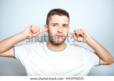 Portrait of a successful man is not listening, isolated on a gray background - stock photo