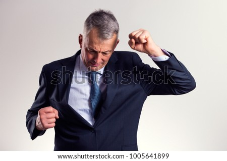 Portrait of a successful mid age businessman who is exulting with tight fists.