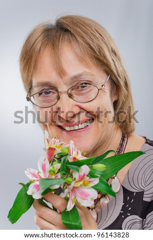 Portrait of a successful senior woman with flowers - stock photo
