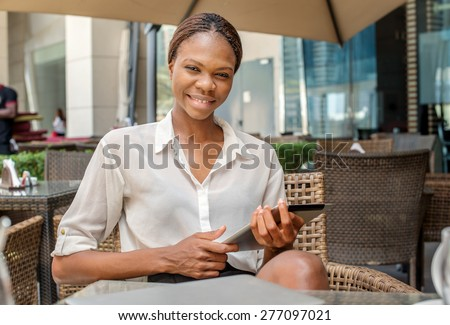 Portrait of a successful woman. African businesswoman businessman holding a cell phone and smiling at the camera in a cafe table in Dubai downtown and drinking coffee - stock photo