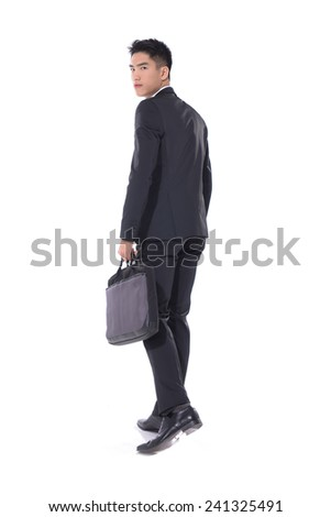 Portrait of a successful young business man carrying a suitcase  - stock photo