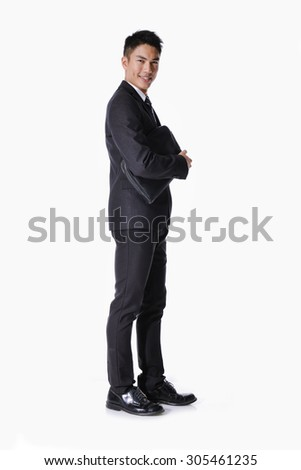 Portrait of a successful young business man carrying a suitcase , full Vertical shot. - stock photo