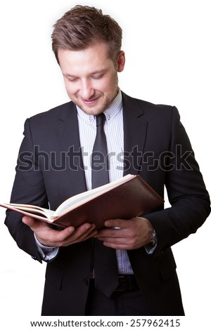 Portrait of a successful young business man holding up book to read isolated on white background - stock photo