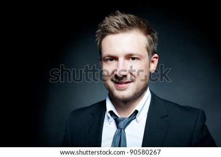 Portrait of a successful young business man on a dark background - stock photo