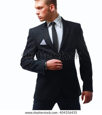 Portrait of a successful young business man standing isolated on grey background - stock photo