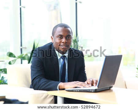 Portrait of a successful young business man working on the laptop - stock photo