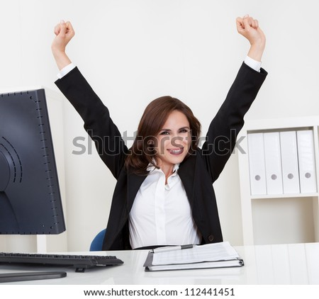 Portrait of a successful young businesswoman with clenched fists at computer desk - stock photo