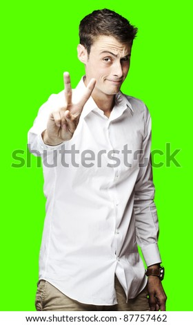 portrait of a successful young man doing good symbol over a removable chroma key background