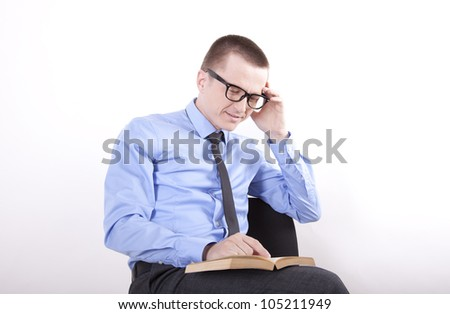 Portrait of a successfull young business man reading book.