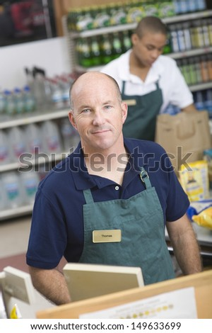 Portrait of a supermarket employee and checkout assistant - stock photo