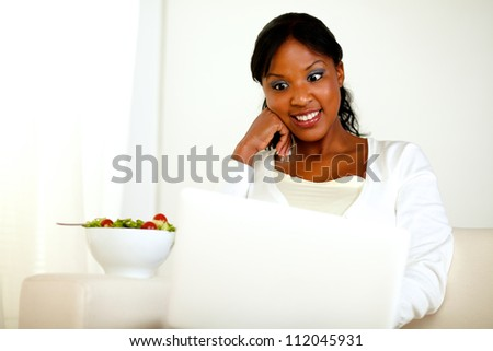 Portrait of a surprised adult woman eating fresh vegetable salad while is sitting in front of her laptop. with copyspace - stock photo