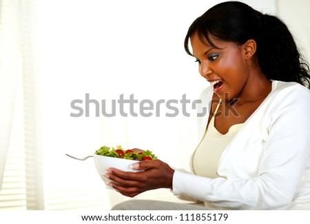 Portrait of a surprised beautiful woman holding and looking to a green salad bowl on light background. With copyspace. - stock photo