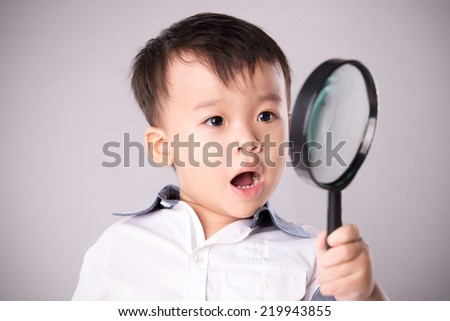Portrait of a surprised boy with magnifying glass. Schoolboy holding the magnifying glass isolated on white  - stock photo