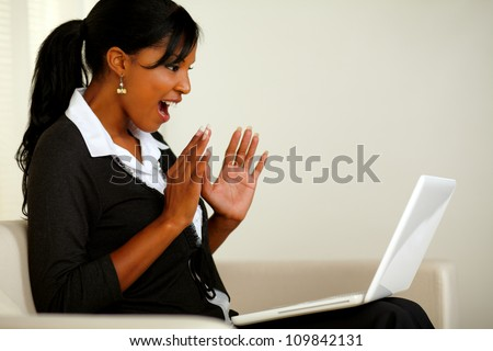 Portrait of a surprised executive young woman reading a great business news on laptop while sitting on couch - stock photo