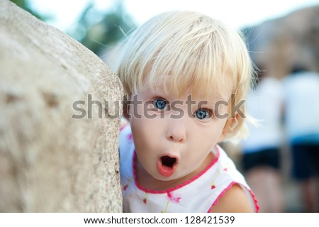 portrait of a surprised girl by the stone