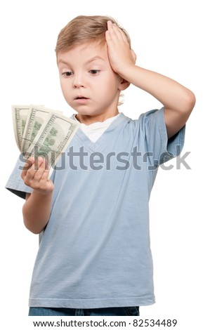 Portrait of a surprised little boy holding a dollars over white background - stock photo