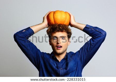 Portrait of a surprised man with pumpkin on head - stock photo