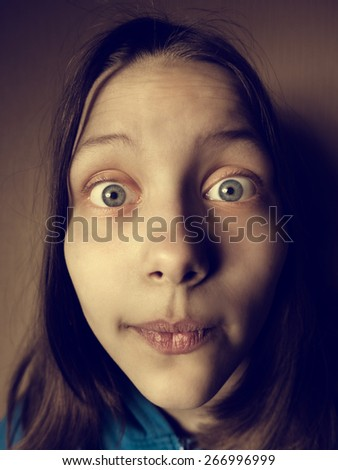 Portrait of a surprised teen girl, studio shot - stock photo
