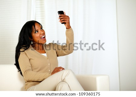 Portrait of a surprised woman holding her cellphone up while is reading a message at home indoor - stock photo