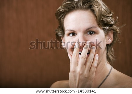 Portrait of a surprised woman in a studio setting - stock photo