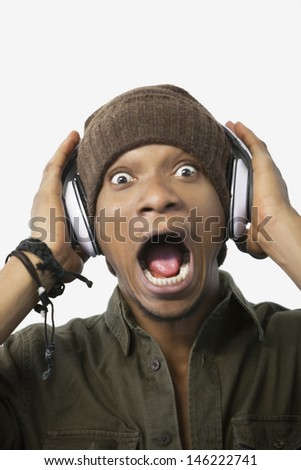 Portrait of a surprised young African American man listening music through headphones - stock photo