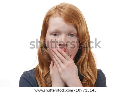 Portrait of a surprised young girl covering her mouth with hands - stock photo
