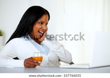 Portrait of a surprised young woman having fun on laptop screen at soft colors composition - stock photo