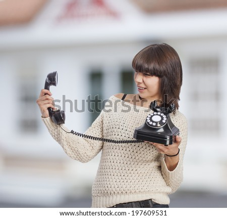portrait of a surprised young woman picking up the phone - stock photo
