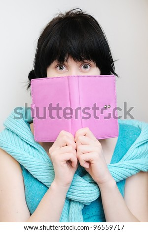 Portrait of a surprised young woman with diary - stock photo
