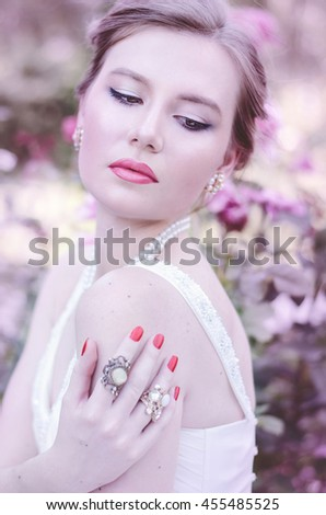 portrait of a sweet, attractive, gentle, romantic, sensual girl in a romantic hairstyle, wearing a white dress. She stands at the bush blooming roses. Bride for a walk in the garden. - stock photo